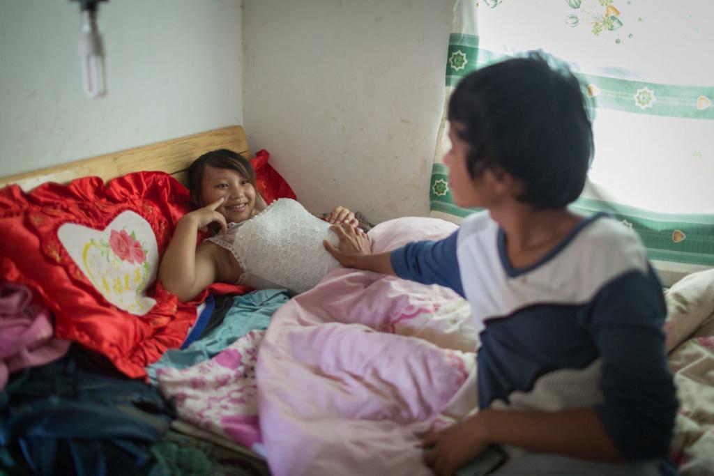 Xiao Wen, di 18 anni, accarezza la pancia di sua moglie Xiao Jie, 13 anni, circa al sesto mese di gravidanza, nella loro casa nel villaggio di Tangzibian, Cina – 3 novembre 2014 - © Mury Xiao