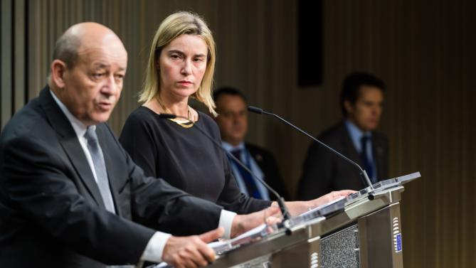European Union High Representative for Foreign Affairs and Security Policy Federica Mogherini, right, and France's Defense Minister Jean-Yves Le Drian address the media during an EU foreign and defense ministers meeting at the EU Council building in Brussels on Tuesday, Nov. 17, 2015. France has demanded that its European partners provide support for its operations against the Islamic State group in Syria and Iraq and other security missions in the wake of the Paris attacks. (AP Photo/Geert Vanden Wijngaert)