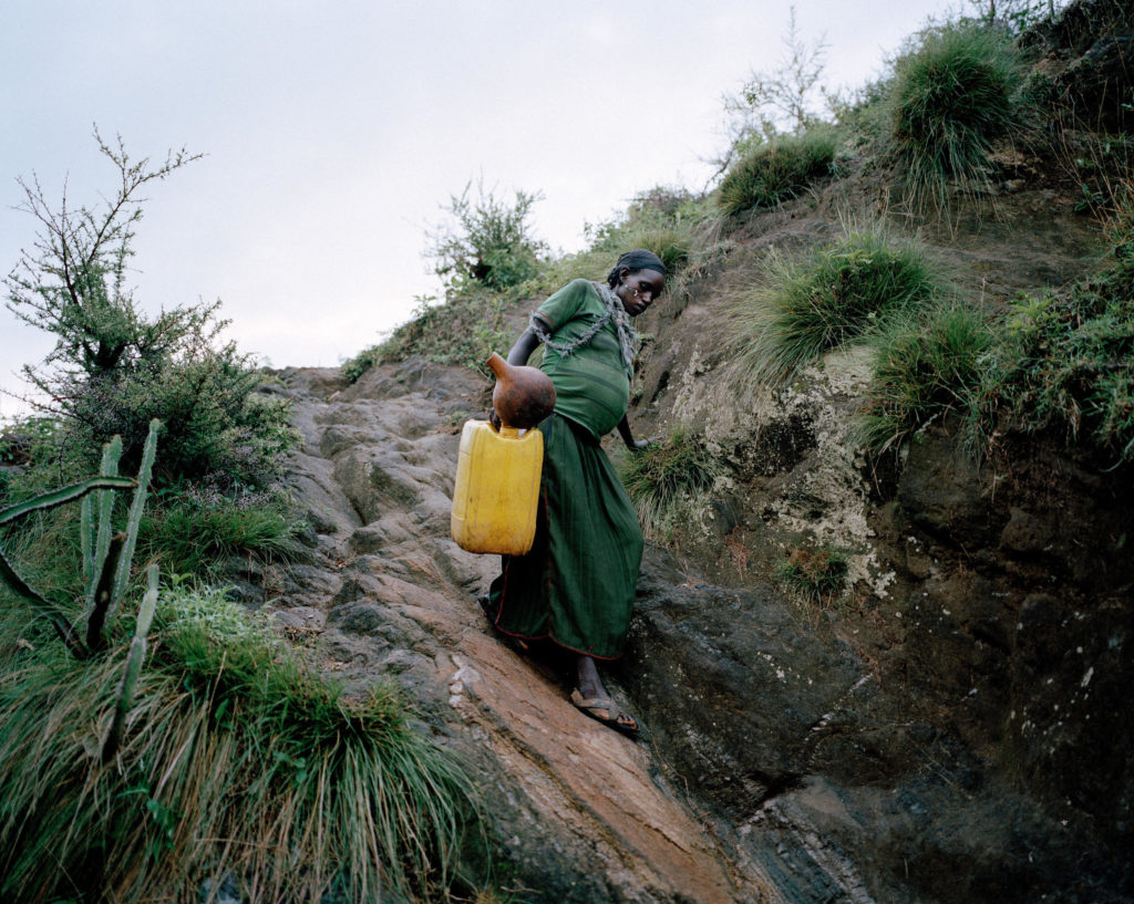 Uchiya, 29, eight months pregnant, carries an empty jerry can from her mountaintop home to a source of water below. She'll fill it with five gallons and then climb back up. In sub-Saharan Africa, women spent 40 billion hours a year collecting water.
