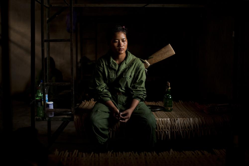 Le lacrime scendono sul viso di una ragazza seduta sul suo letto, appena dopo l'addestramento militare del mattino, nel quartier generale della quinta brigata del KIA, fuori da Laiza, nello stato del Kachin, Myanmar, maggio 2013. Le donne arruolate nell'esercito guadagnano 10.000 Kyat al mese (circa 10 dollari) e spesso, dopo essersi arruolate, possono andarsene soltanto per sposarsi © Adriane Ohanesian