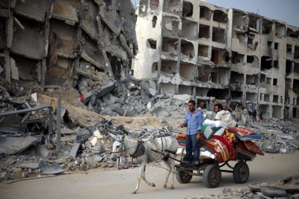 Palestinians ride a donkey cart past destroyed and badly damaged residential buildings as they return to Beit Lahiya town, which witnesses said was heavily hit by Israeli shelling and air strikes during the Israeli offensive, in the northern Gaza Strip August 5, 2014. Israel pulled its ground forces out of the Gaza Strip on Tuesday and began a 72-hour truce with Hamas mediated by Egypt as a first step towards negotiations on a more enduring end to the month-old war. Gaza officials say the war has killed 1,834 Palestinians, most of them civilians. Israel says 64 of its soldiers and three civilians have been killed since fighting began on July 8, after a surge in Palestinian rocket launches. REUTERS/Suhaib Salem