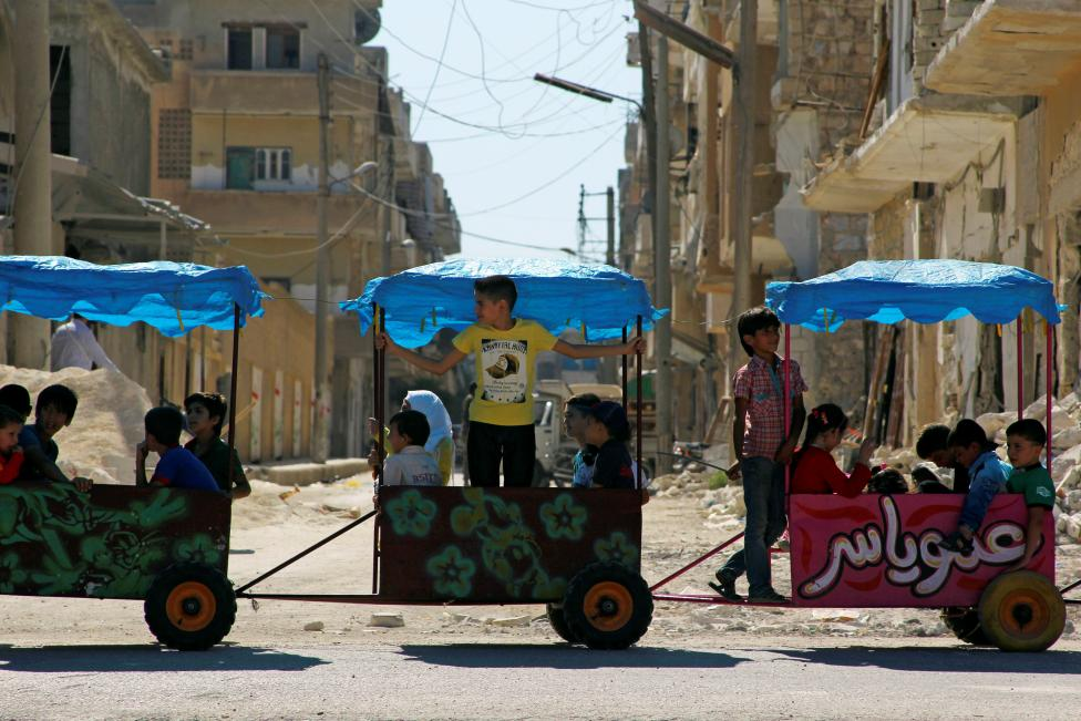 Children ride in carts on the third day of Eid al-Adha in the rebel controlled city of Idlib, Syria September 14, 2016. REUTERS/Ammar Abdullah