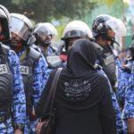 Una sostenitrice dell'opposizione maldiviana si trova di fronte alla polizia durante una protesta. Credits to: AP.